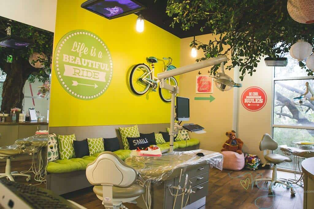 Hill Country Pediatric Dentistry and orthodontics office treatment area under a big tree with white and beige Chinese lamps balls view of the big real pair of bicycle hanging on the bright yellow wall along with a round retro style lime green colored sign with dotted frame in white and an arrow pointing right, saying: Life is a Beautiful Ride written in white positioned above a long seating bench covered with lime green base cushion and back cushions in lime green, black and white variation, a few other office signs in red and white visible on adjacent wall