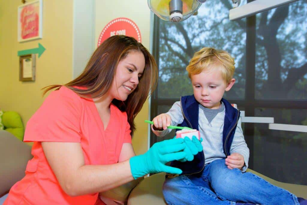 A young patient wearing blue jeans a gray sweatshirt and a blue open zippered vest holding a large sized green tooth brush is brushing the teeth of a gum and teeth model held by a team members of Hill Country Pediatric Dentistry and orthodontics office wearing orange office uniform and green exam gloves sitting next to the treatment bed on which the blond hair boy is sitting, the view of a few retro style red background with white writing office decor signs are visible on the wall behind them