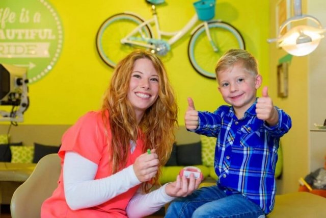 A young patient wearing blue jeans and a blue plaid flannel shirt signaling holding both his thumbs up sitting on a treatment bed and a smiling team members of Hill Country Pediatric Dentistry and orthodontics office wearing orange office uniform holding a large sized green tooth brush and a gum and teeth model sitting next to the treatment bed on which the boy is, view of the big real pair of bicycle hanging on the bright yellow wall along with a round retro style lime green colored sign with dotted frame in white and an arrow pointing right, saying: Life is a Beautiful Ride written in white positioned above a long seating bench covered with lime green base cushion and back cushions in lime green, black and white varied patterns on the wall behind them
