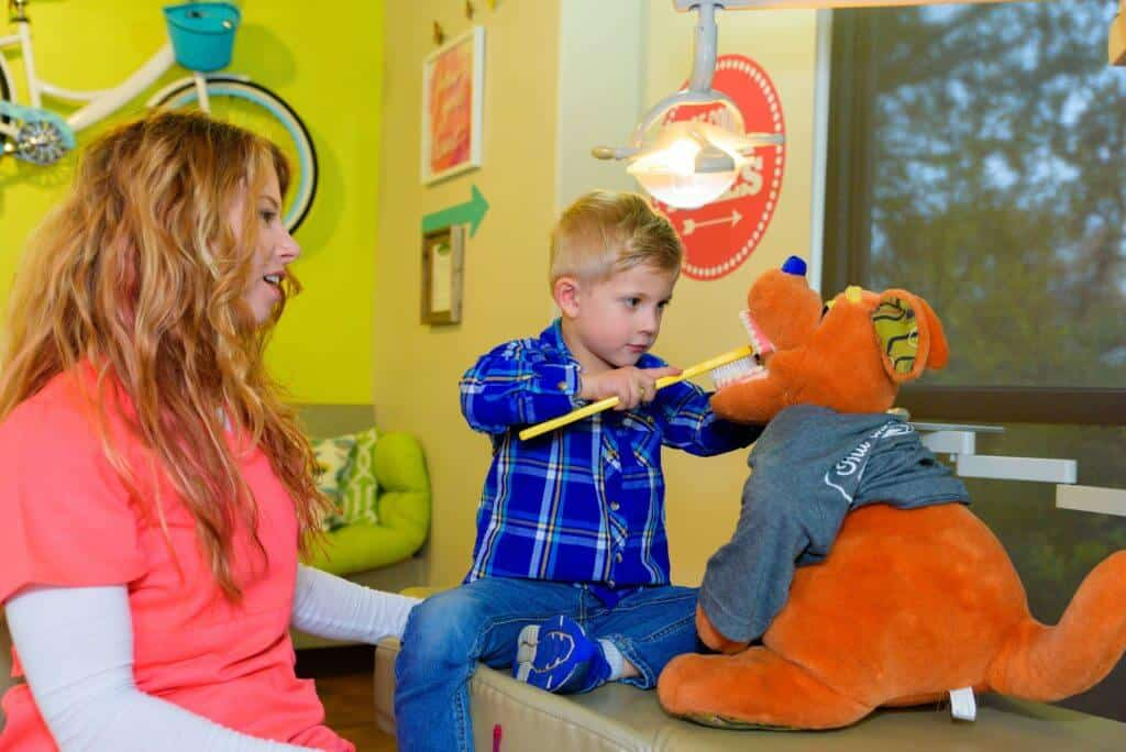 A young patient wearing blue jeans and a blue plaid flannel shirt holding a huge sized yellow tooth brush to brush the teeth of a child size office orange kangaroo stuffed figure who is wearing a gray tee shirt while both are sitting on the treatment bed with one of the team members of Hill Country Pediatric Dentistry and orthodontics office is supervising the boy, the view of the yellow bright wall behind her with part of the bicycle hanging from the wall is visible and a few retro style red background with white writing office decor signs are visible on the other wall